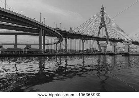 Black and White Suspension bridge over white watergate river front Bangkok Thailand
