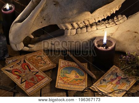 Close up of the tarot cards, black candles and skull. Mystic still life with scary occult objects, horror Halloween and black magick concept, fortune telling or divination rite