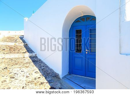 Bright blue doors, shutters and perfect white washed walls in back streets of Akrotiri, Santorini, Greece.