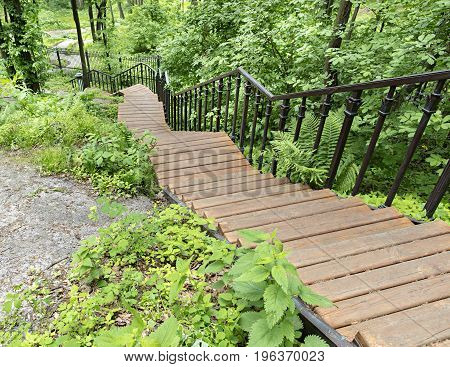 A wooden staircase with figured metal railing descends down the grove a lighted park path goes down the hillside bending around a large stone boulder