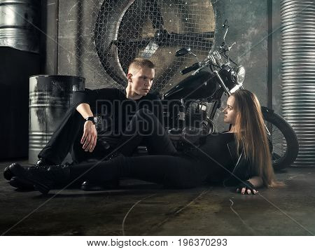 Girl and guy bikers in the garage. expressive interior. Beautiful motorcycle