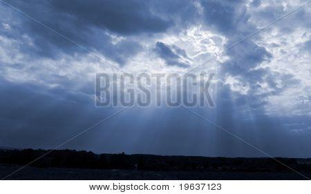 Sun rays in dark blue sky