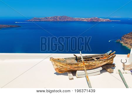 Old boat with oars on the bright white roof. Deep blue sea and volcanic island on the background. Santorini, Greece.