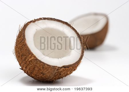 Closeup of cracked coconut on white background with light shadow. Shallow focus depth on front coconut