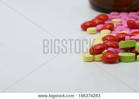 Colorful of vitamin tablets on white background