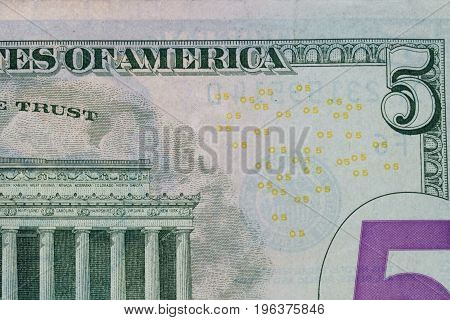 Focus on five dollar bank note, background