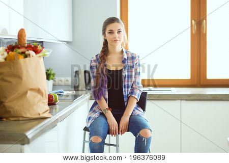 Portrait of young woman standing with arms crossed against kitchen background.