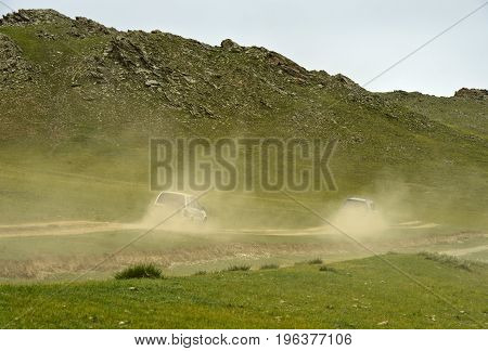 Two four-wheel-drive vehicles with tourists on a dusty dirt road Orkhon Valley Cultural Landscape Mongolia