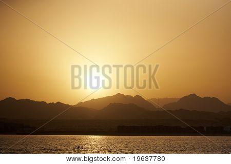 Sunset landscape - sea, mountains, yellow sky