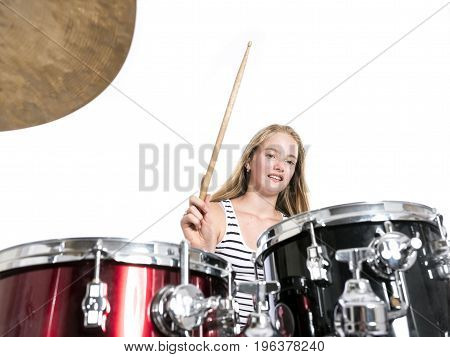 young blond caucasian teenage girl plays the drums in studio against white background