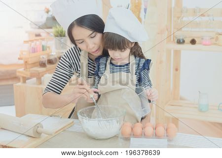 Happy Family In The Kitchen. Asian Mother And Her Daughter Preparing The Dough To Make A Cake.photo
