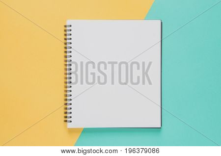 Office Workplace Minimal Concept. Blank Notebook On Yellow And Blue Background.