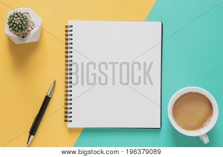 Office workplace minimal concept. Blank notebook with cup of coffee cactus pencil on yellow and blue background. Top view with copy space flat lay. Pastel color filter.