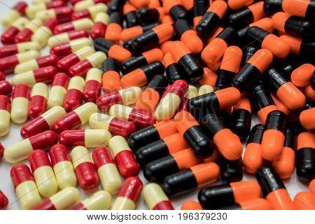 Orange black red pale yellow capsule pills