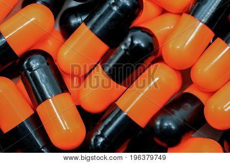 Top view of orange black capsule pills