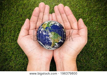 earth by nasa in hand on grass background, earth day concept, elements of this image furnished by NASA