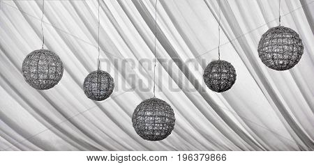 Decorative hanging silver lamps and curtains on the ceiling
