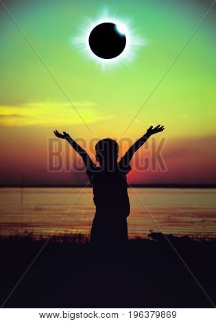 Amazing scientific natural phenomenon. Silhouette back view of child looking at total solar eclipse glowing on sky at seaside. Boy enjoying view and raising his hands up. Cross process.