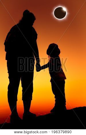 Amazing scientific natural phenomenon. Silhouette back view of Mother and daughter looking at total solar eclipse glowing on orange sky at mountaintop. Happy family spending time together.