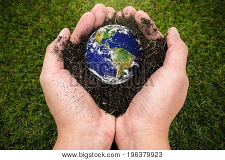 Soil  and earth by nasa in hand on grass background, earth day concept, elements of this image furnished by NASA