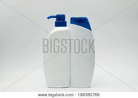 Shampoo and conditioner bottles with blue cap on white background