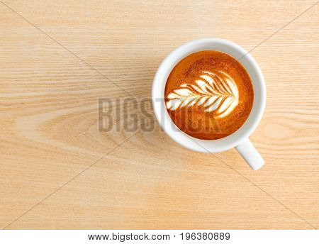 Above capture of white coffee cup with tree shape latte art on wood table at cafe
