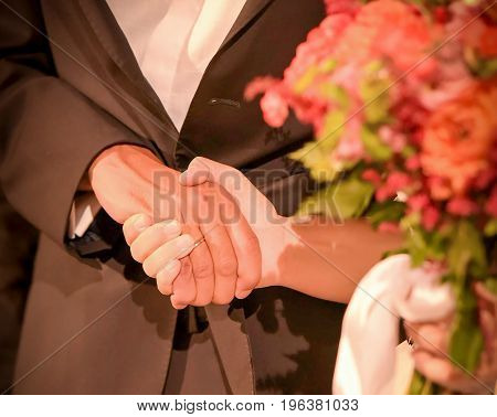 bride holding wedding bouquet and with her other hand holding grooms hand