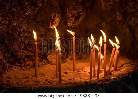 Lighting candles on rocks inside a cave orthodox chapel .Greece