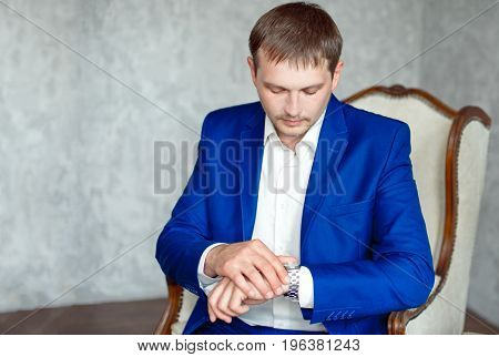 Handsome young elegant man in suit, relaxing, sits on arm chair. Brown background, silver watch, white shirt, blue suit.