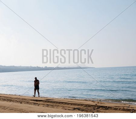 Old man walking along a beach at sunset. Tropical beach. Summer background. Selective focus.