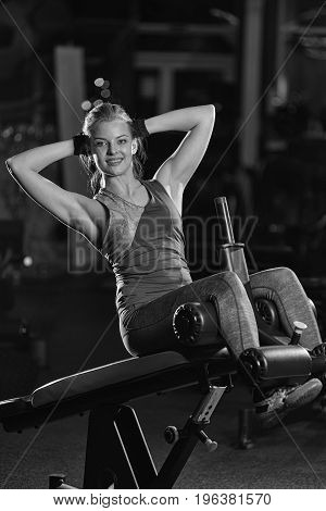 Woman doing strength exercises for abdominal muscles at indoor sport gym. Girl doing yoga stretches after running. Fitness model in dark sport club. Black and white.