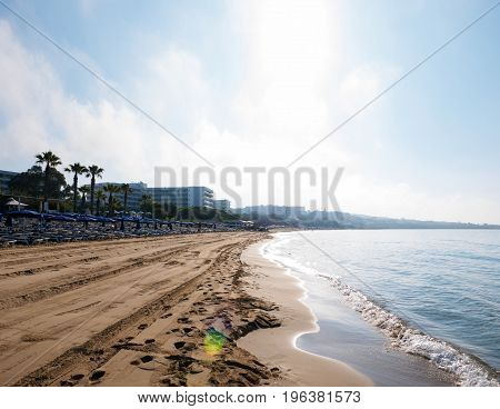 Soft Wave Of Blue Ocean On Sandy Beach. Background. Selective focus. Beach in the morning at sunrise in Ayia Napa on the island of Cyprus. Tropical beach. Summer background.