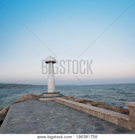 Lighthouse on the embankment near the port. Seascape in the evening. Lighthouse, sea air at night. Seascape at sunset