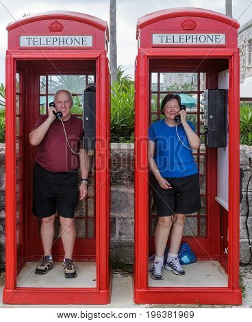 A smiling happy retired couple having fun in old fashioned red English phone booths in Bermuda.