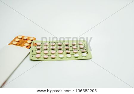 Two blister pack of birth control pills on white background