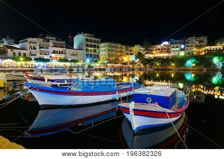 Tourists relax in outdoor restaurant on the shores of lake Voulismeni with a lot of boats
