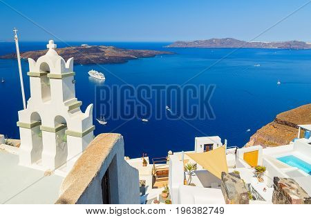 Bell tower of Orthodox church with view over volcanic caldera at Fira, Santorini Island