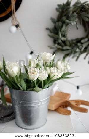 A bouquet of tulips in an iron bowl on a table. Scandinavian interior elements