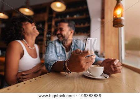 Young couple enjoying at coffee shop. Man holding mobile phone with laughing woman sitting by.