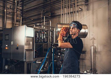 Young Man With Metal Beer Barrels At Brewery
