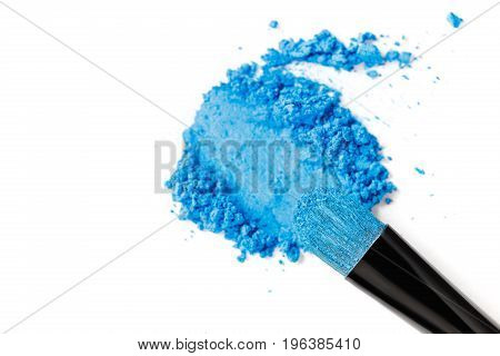 Broken blue eye shadow and brush isolated on the white background