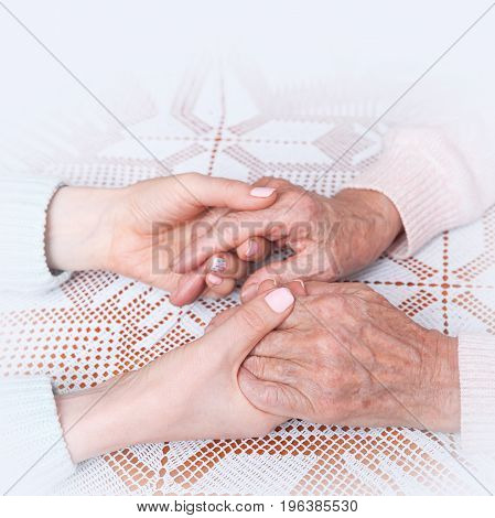 Helping hands, care for elderly concept. Care is at home of elderly.