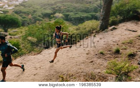 Couple of runners on mountain trail. Young man and woman running in nature. Trail running workout.