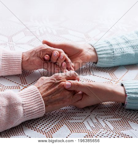 Care is at home of elderly. Holding hands closeup
