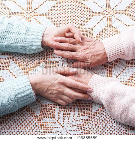 Helping hands, care for the elderly concept Closeup top view.