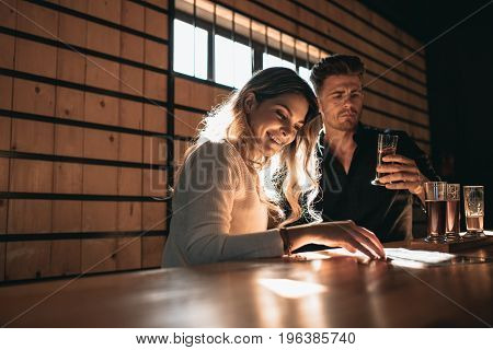 Young couple at the bar tasting different varieties of craft beers. Beautiful young woman with her boyfriend at the bar having beers.