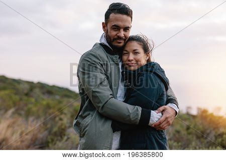Beautiful Young Couple Embracing In Countryside