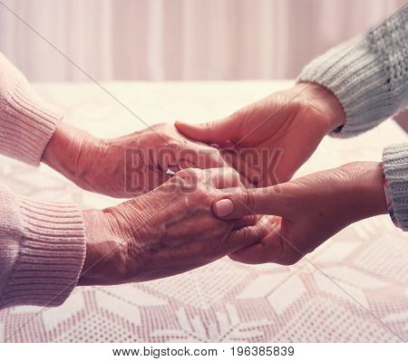 Senior woman with her caregiver at home. Holding hands, horizontally top view
