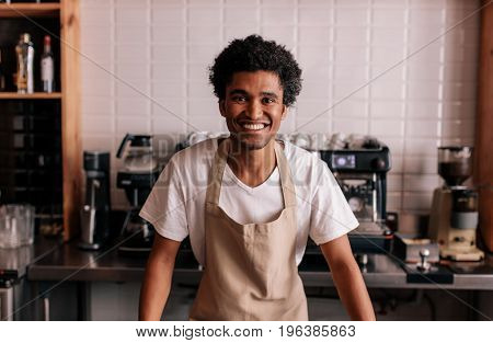 Portrait of happy young barista standing at cafe counter. African man in apron looking at camera and smiling.