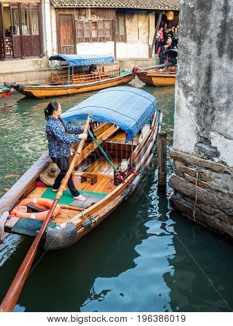 Suzhou, China - Nov 5, 2016: Lady quickly steering and rowing her boat around a canal bend at the historic Zhouzhuang Water Town.